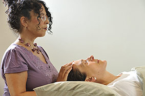Client receiving Reiki at the top of her head (the crown chakra)