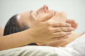 Client receiving Reiki at her throat (the throat chakra)